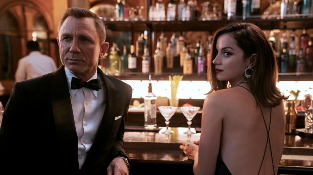 """This image released by MGM shows Daniel Craig, left, and Ana de Armas in a scene from """"No Time To Die,"""" in theaters on Oct. 8. (Nicola Dove/MGM via AP)"""