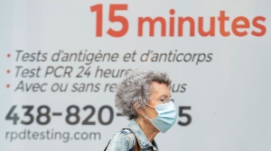 A woman wears a face mask as she walks by a COVID-19 rapid testing business in Montreal, Sunday, September 12, 2021, as the COVID-19 pandemic continues in Canada and around the world. THE CANADIAN PRESS/Graham Hughes