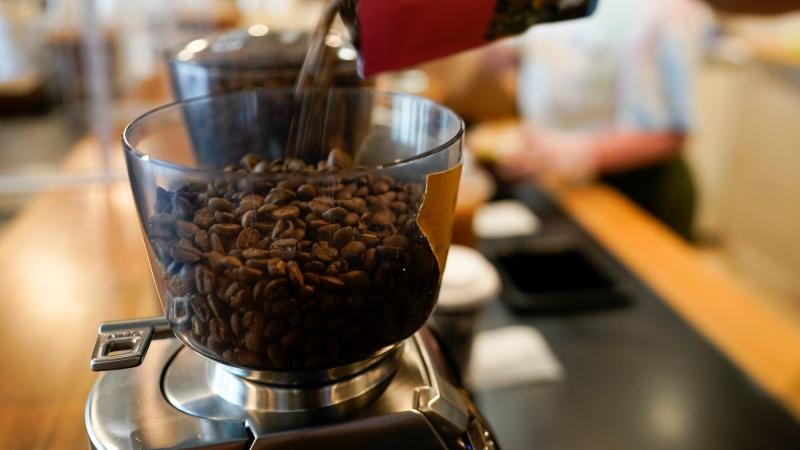 Chris Vigilante refills a coffee grinder with coffee beans at Vigilante Coffee, Wednesday, Sept. 1, 2021, in College Park, Md. (AP Photo/Julio Cortez)
