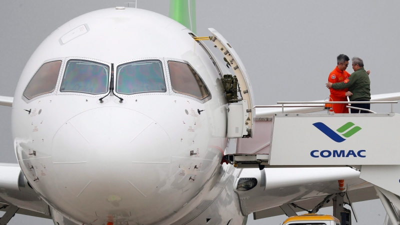 A flight crew member, left, is embraced after disembarking from a Chinese C919 passenger jet after its first flight at Pudong International Airport in Shanghai, China, Friday, May 5, 2017. (AP Photo/Andy Wong, Pool)