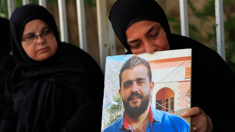 A mother whose son was killed in last year's massive blast at Beirut's seaport, holds a portrait of him during a protest outside judges offices, in Beirut, Lebanon, Monday, July 12, 2021. (AP Photo/Hussein Malla)