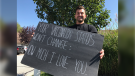 Zachery Dereniowski holds up the sign he made to send a positive vaccination message in LaSalle, Ont. on Monday, Sept. 27, 2021. (Michelle Maluske/CTV Windsor)