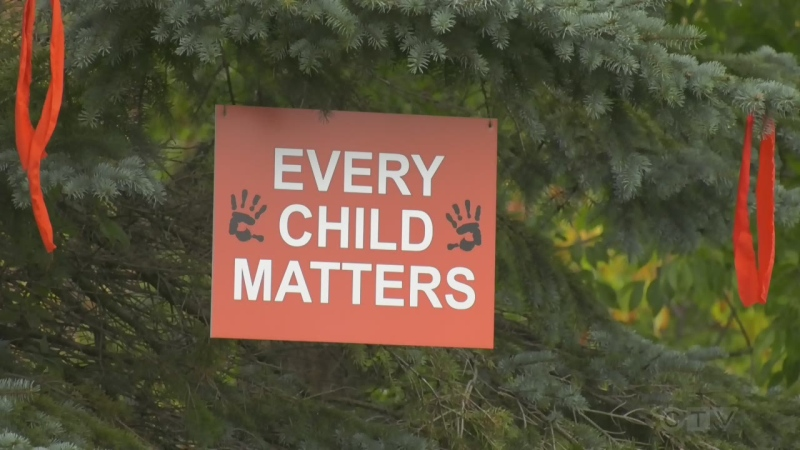 A tree in a Huntsville, Ont., park has orange ribbons hanging from it with a sign, Every Child Matters, on Mon., Sept. 27, 2021 (Katelyn Wilson/CTV News)
