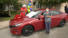 Personal Support Worker Sonia Botas wins a new car in a vaccine contest in Bradford West Gwillimbury, Ont., on Mon., Sept. 27, 2021, donated by Raptors superfan Nav Bhatia. (Kraig Krause/CTV News)