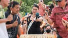 Nakuset, centre, executive director of the native women's shelter of Montreal holds a microphone for drummers during a gathering and march to honour Indigenous children, denounce genocide and demand justice for residential school victims in Montreal, Thursday, July 1, 2021.THE CANADIAN PRESS/Graham Hughes