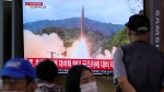 People watch a TV showing a file image of North Korea's missile launch during a news program at the Seoul Railway Station in Seoul, South Korea, Sept. 28, 2021. (AP Photo/Ahn Young-joon)