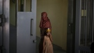 Razia and her 6-year-old daughter Alia, stand inside the women's section of the Pul-e-Charkhi prison in Kabul, Afghanistan, Thursday, Sept. 23, 2021. (AP Photo/Felipe Dana)