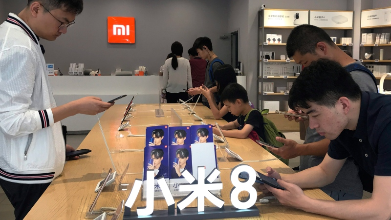 In this Wednesday, June 20, 2018, photo, People try out the Xiaomi latest smartphones on display at the Xiaomi store in Beijing. (AP Photo/Andy Wong)
