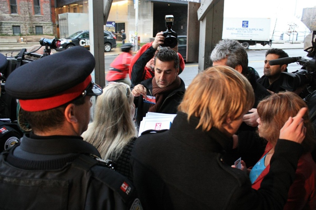Realtors are handed numbers after waiting in line for a chance to buy a condo at a new development at Jarvis and Bloor Streets, Wednesday, Nov. 25, 2009.