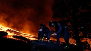 Military Emergency Unit personal take gas reading measurements near a volcano on the Canary island of La Palma, Spain, in the early hours of Sept. 28, 2021. (Luismi Ortiz / UME, via AP)