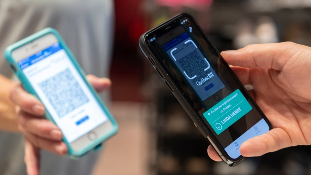 Linda Henry has her COVID-19 QR code scanned by Jonathan Gagne, manager of Orangetheory Fitness in Montreal, Wednesday, September 1, 2021, as the Quebec government's COVID-19 vaccine passport comes into effect. THE CANADIAN PRESS/Graham Hughes