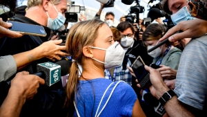 Swedish climate activist Greta Thunberg, centre, is surrounded by members of the media as she arrives for the Youth4Climate summit in Milan, Italy, on Sept. 28, 2021. (Claudio Furlan / LaPresse via AP)