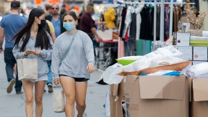 People wear face masks at they walk next to stalls set out for a sidewalk sale on Ste-Catherine Street in Montreal, Sunday, September 12, 2021, as the COVID-19 pandemic continues in Canada and around the world. THE CANADIAN PRESS/Graham Hughes