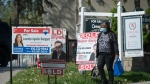 A women wearing a mask walks past real estate listings during the COVID-19 pandemic in Mississauga, Ont., on Tuesday, May 26, 2020. THE CANADIAN PRESS/Nathan Denette