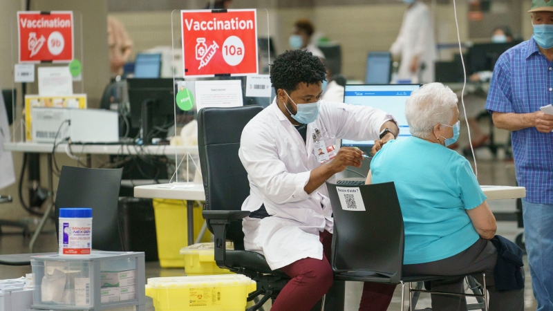 A woman is vaccinated at a COVID-19 vaccination clinic in Montreal, on Monday, June 21, 2021. THE CANADIAN PRESS/Paul Chiasson