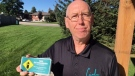 Tony Bendel, who organizes the Cindy's Law campaign, is seen holding stickers available at Home Hardware locations in St. Thomas and St. Marys on Tuesday, Sept. 28, 2021. (Sean Irvine / CTV News)