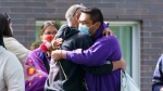 Carol Dube, husband of Joyce Echaquan, is hugged as he arrives for a memorial marking the first anniversary of the death of his wife in Joliette, Que. on Tuesday, September 28, 2021. The 37-year-old Atikamekw mother of seven was humiliated by hospital staff just before she died. THE CANADIAN PRESS/Paul Chiasson