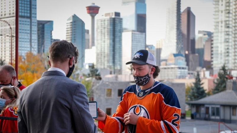 An Edmonton Oiler fan has their COVID-19 vaccination proof checked before entering the Saddledome for pre-season NHL hockey action in Calgary, Alta., Sunday, Sept. 26, 2021. THE CANADIAN PRESS/Jeff McIntosh