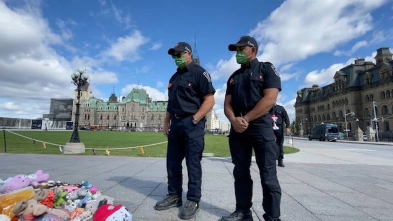 Ottawa Fire Services volunteer firefighters Tim Baptiste (left) and David Remo (right) show solidarity at the Centennial Flame on Parliament Hill in Ottawa, Tuesday, Sept. 28, 2021. (Peter Szperling/CTV News Ottawa)