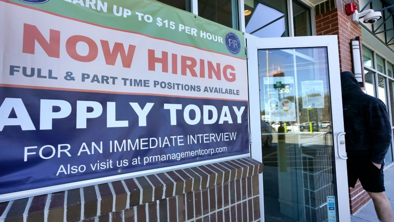 """A man walks into a restaurant displaying a """"Now Hiring"""" sign, Thursday, March 4, 2021, in Salem, N.H. (AP Photo/Elise Amendola)"""