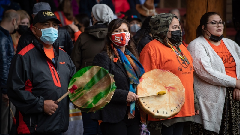 Chief Rosanne Casimir, second left, plays a drum during a ceremony to honour residential school survivors and mark the first National Day for Truth and Reconciliation, in Kamloops, BC., on Thursday, September 30, 2021. THE CANADIAN PRESS/Darryl Dyck