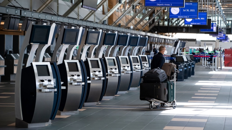 A traveller waits next to check-in kiosks not currently in use at Vancouver International Airport, in Richmond, B.C., on Friday, July 30, 2021. (THE CANADIAN PRESS / Darryl Dyck)