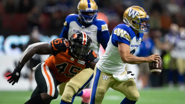 Winnipeg quarterback Zach Collaros, right, gets away from B.C.'s Tim Bonner during the first half of the Blue Bombers' 30-9 win over the Lions on Friday. (Darryl Dyck/The Canadian Press)