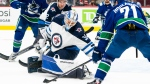 Winnipeg Jets goalie Mikhail Berdin (left) scrambles to stop Vancouver Canucks' Nils Hoglander during second period NHL preseason hockey action in Vancouver, Sunday, Oct. 3, 2021. (THE CANADIAN PRESS/Richard Lam)