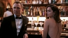 """This image released by Metro Goldwyn Mayer Pictures shows Daniel Craig, left, Ana de Armas in a scene from """"No Time To Die."""" (Nicola Dove/Metro Goldwyn Mayer Pictures via AP)"""