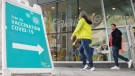 People walk by a sign advertising a COVID-19 vaccination site, in Montreal, Sunday, Oct. 3, 2021. THE CANADIAN PRESS/Graham Hughes