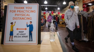 Erin Connolly wears a mask to protect them from the COVID-19 virus while looking at clothes at Trailhead in Kingston, Ontario, on Wednesday Feb. 10, 2021. ( THE CANADIAN PRESS/Lars Hagberg)