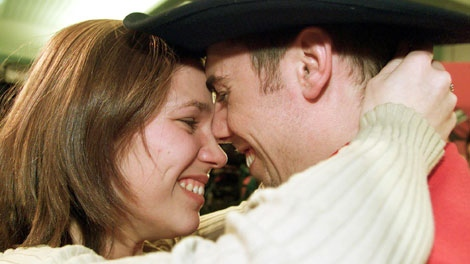 Canadian speed skater Eric Bedard gets a kiss from his girlfriend, Veronique Martel, after arriving at Dorval Airport in Montreal Tuesday, Feb. 26, 2002. (Ryan Remiorz / THE CANADIAN PRESS)