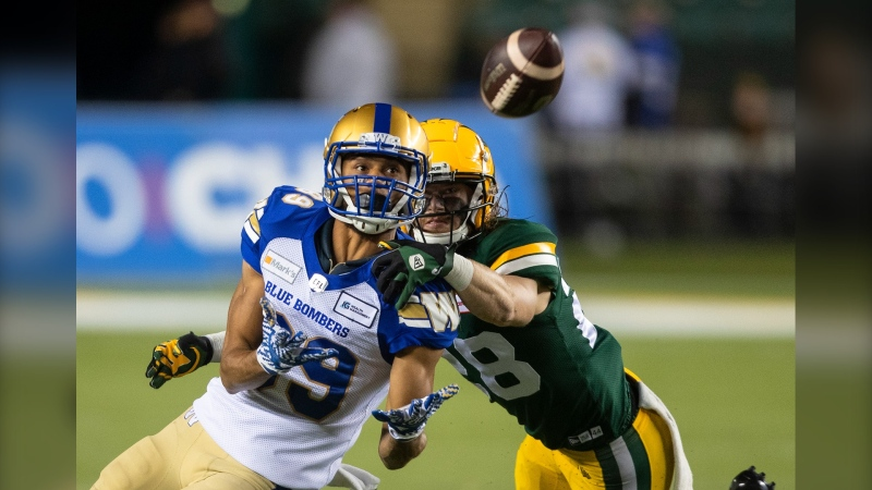 Winnipeg Blue Bombers' Kenny Lawler (89) reaches for the ball as Edmonton Elks' Jordan Hoover (28) defends during second half CFL action in Edmonton, Alta., on Saturday September 18, 2021. THE CANADIAN PRESS/Jason Franson.