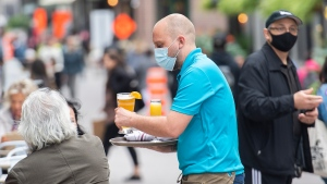 A server wears a face mask as he brings a beer to a customer on an outdoor terrace at a restaurant in Montreal, Sunday, Oct. 3, 2021, as the COVID-19 pandemic continues in Canada and around the world. THE CANADIAN PRESS/Graham Hughes