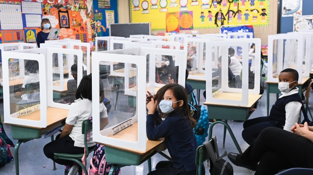 Children wearing masks sit behind screened in cubicles as they learn in their classroom after getting their pictures taken at picture day at St. Barnabas Catholic School during the COVID-19 pandemic in Scarborough, Ont., on Tuesday, October 27, 2020. THE CANADIAN PRESS/Nathan Denette