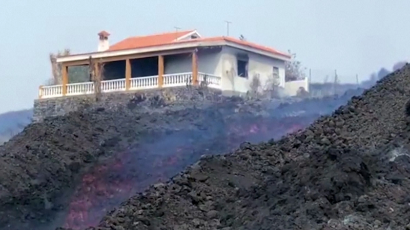 Lava from the Cumbre Vieja volcano in Spain flow past an abandoned house as magma reportedly destroyed four buildings on Oct. 9.