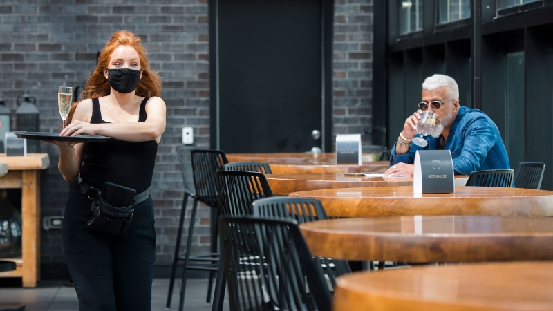 FILE - Patrons sit on the patio as waitress Susie Plamondon, left, carries a glass of champagne at Joey Sherway, part of the Joey Restaurant chain during the COVID-19 pandemic in Toronto on Wednesday, June 24, 2020. THE CANADIAN PRESS/Nathan Denette