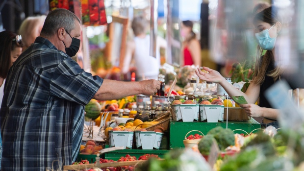 People wear face masks as they shop at a market in Montreal, Saturday, July 24, 2021, as the COVID-19 pandemic continues in Canada and around the world. THE CANADIAN PRESS/Graham Hughes