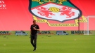 In this photo provided by Wrexham FC, Wrexham manager Phil Parkinson is seen in front of the new Kop banner the Racecourse Ground in Wrexham, Wales, Saturday, Sept. 18, 2021. (Gemma Thomas/Wrexham FC via AP)