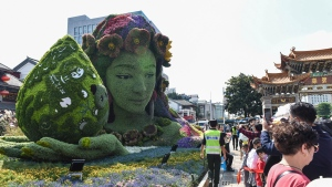 Tourists pass by a floral decoration celebrating the UN Biodiversity Conference (COP 15) in a park in Kunming, the host city, in southwestern China's Yunnan province, on Oct. 2, 2021. (Chinatopix via AP)