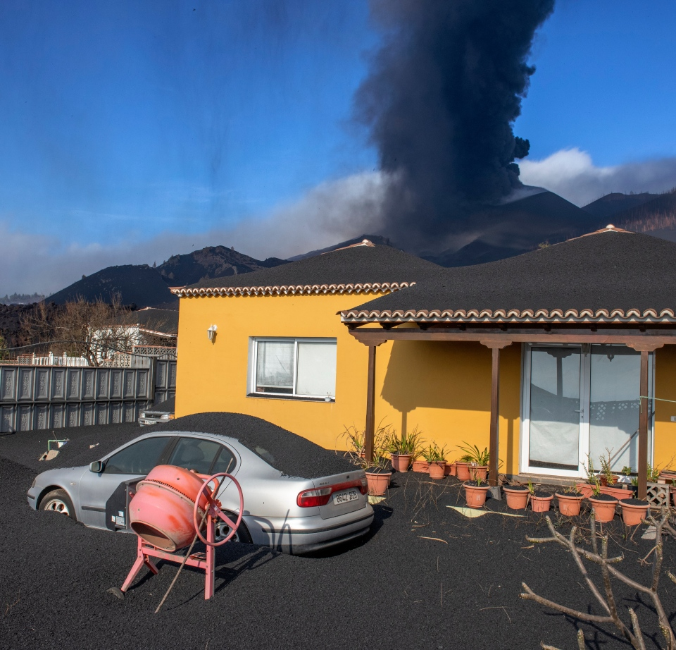 Ash covers a house, car and garden in La Palma