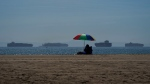 Container ships waiting to dock at the Ports of Los Angeles and Long Beach are seen from a beach in Seal Beach Calif., on Oct. 1, 2021. (Jae C. Hong / AP)