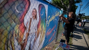 A woman places a decoration near a poster after attending the funeral home viewing of Gabby Petito at Moloney's Funeral Home in Holbrook, N.Y., on Sept. 26, 2021. (Eduardo Munoz Alvarez / AP)