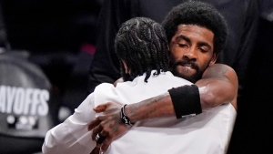 Brooklyn Nets guard Kyrie Irving, right, embraces injured Nets forward James Harden in New York, on June 7, 2021. (Kathy Willens / AP)