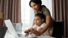 A family looks at a computer in this stock image. (Pexels)