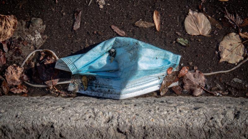 A discarded mask litters the street. (Photo by Elizabeth McDaniel on Unsplash)