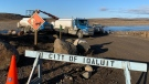 Trucks work by the Sylvia Grinnell River near Iqaluit, Nunavut on Wednesday, Oct. 13, 2021 after potential petroleum was discovered in the city's tap water, making it undrinkable. THE CANADIAN PRESS/Emma Tranter