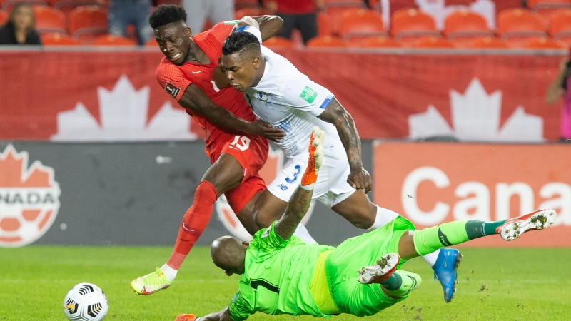 Canada's Alphonso Davies, left, runs around Panama goalkeeper Luis Mejia as Harold Cummings looks on during first half World Cup qualifying action in Toronto, Oct. 13, 2021. THE CANADIAN PRESS/Chris Young