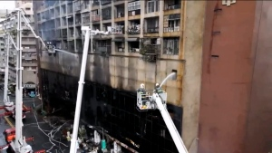 In this image taken from video by Taiwan's EBC, firefighters shoot water into a building that caught fire in Kaohsiung, in southern Taiwan on Thursday, Oct. 14, 2021. (EBC via AP)