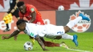 Canada's Alphonso Davies goes down under Harold Cummings' challenge during first half World Cup qualifying action in Toronto on Wednesday, October 13, 2021. THE CANADIAN PRESS/Chris Young